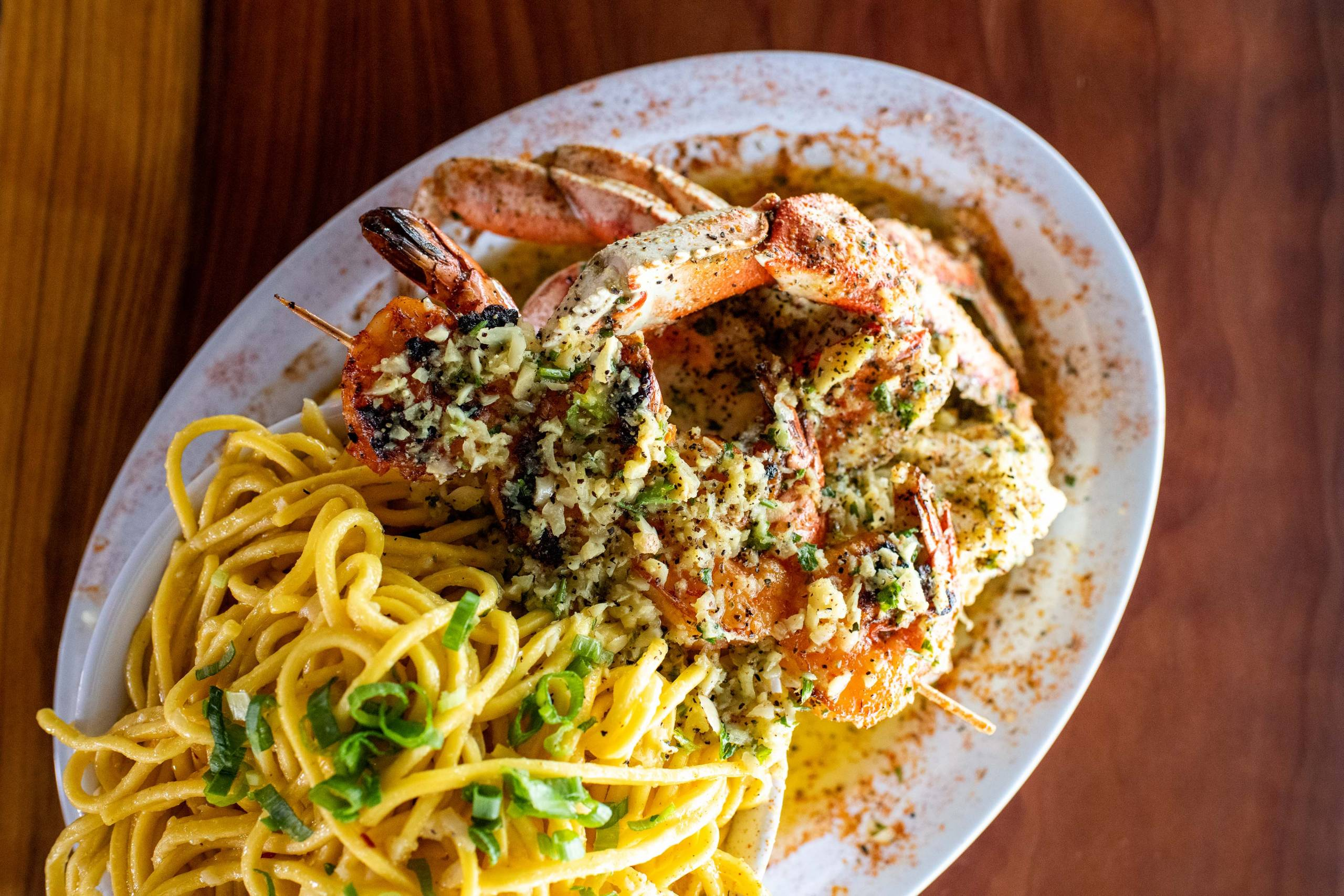 Overhead view of a plate of garlic noodles and roast crab.