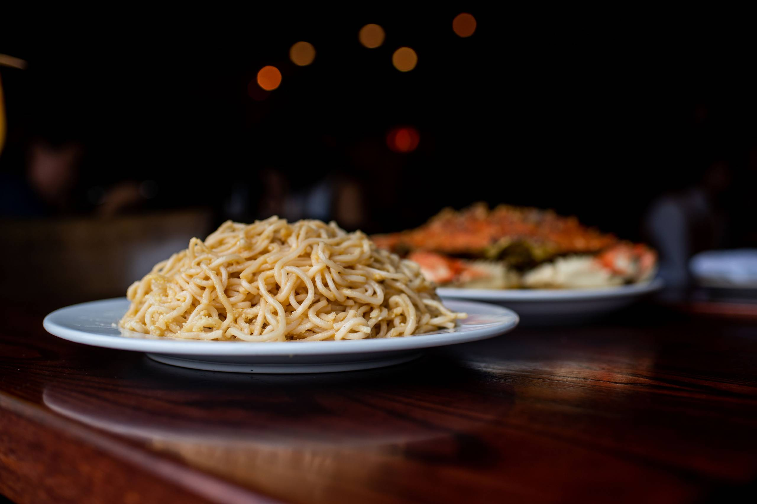 A plate piled high with garlic noodles on a table, in front of a plate of whole roast crab.