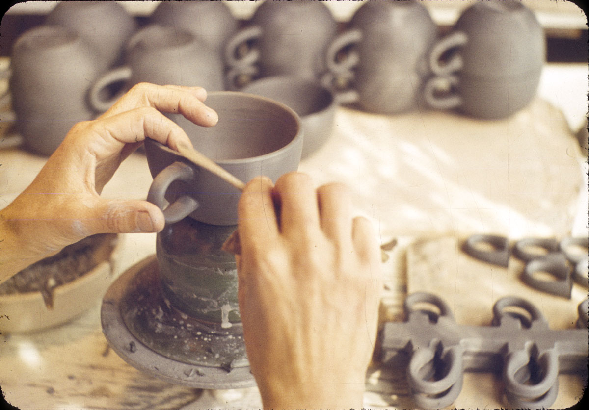 Light-skinned hands use a tool on a dark clay teacup.