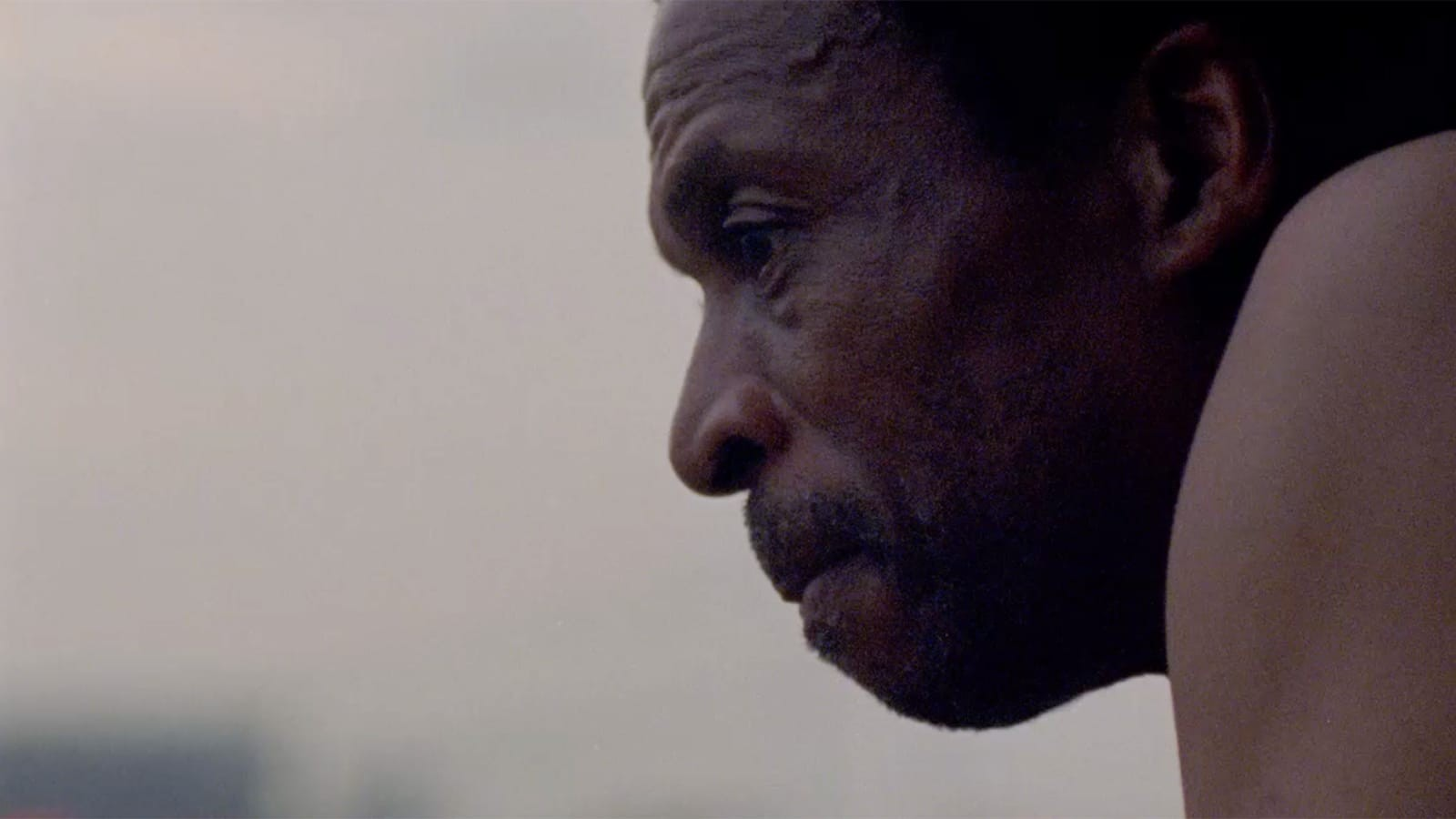 A close-up of a dark-skinned man in profile.