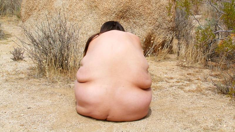 Woman's bare back in front of tan rock.