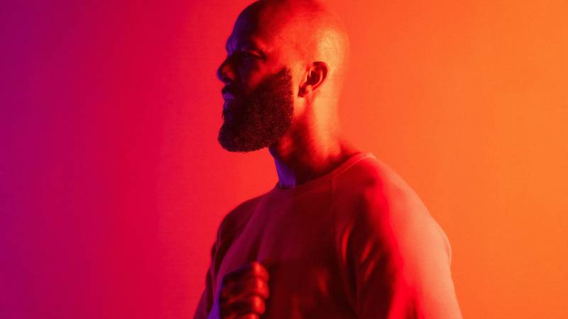 The rapper common in profile against a gradient violet-orange background
