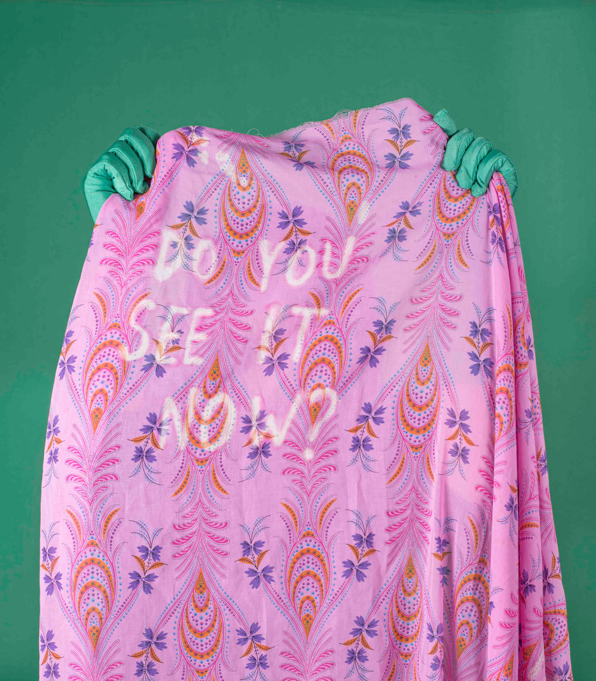 Green hands hold up a pink-patterned fabric with the text: Do you see it now?