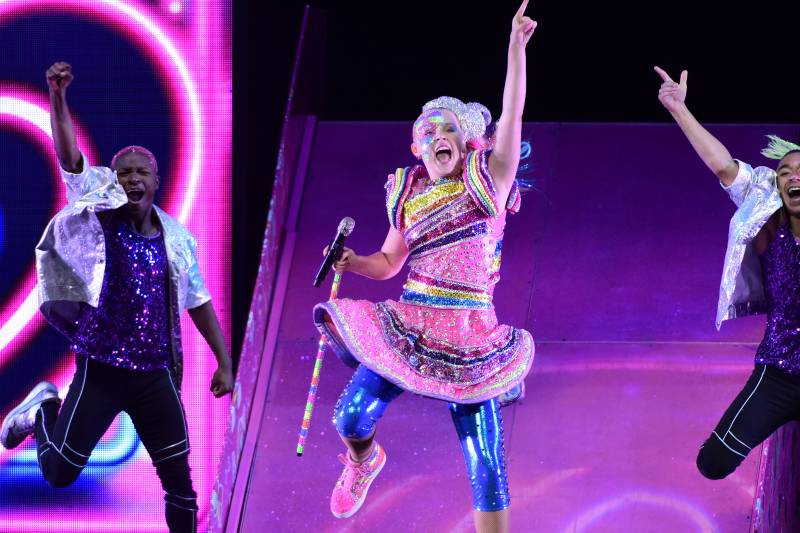 JoJo Siwa, dancing, one arm in the arm, mouth open singing, wearing a sparkling rainbow dress with large shoulder features, and shiny blue leggings underneath.