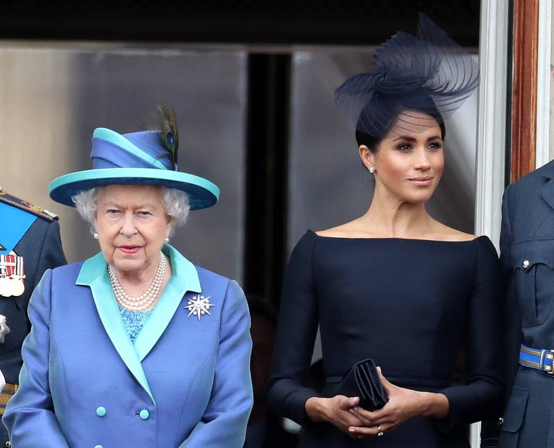 Queen Elizabeth, wearing a lilac and green suit and hat, stands beside Meghan Markle, who's wearing a navy dress and matching fascinator.