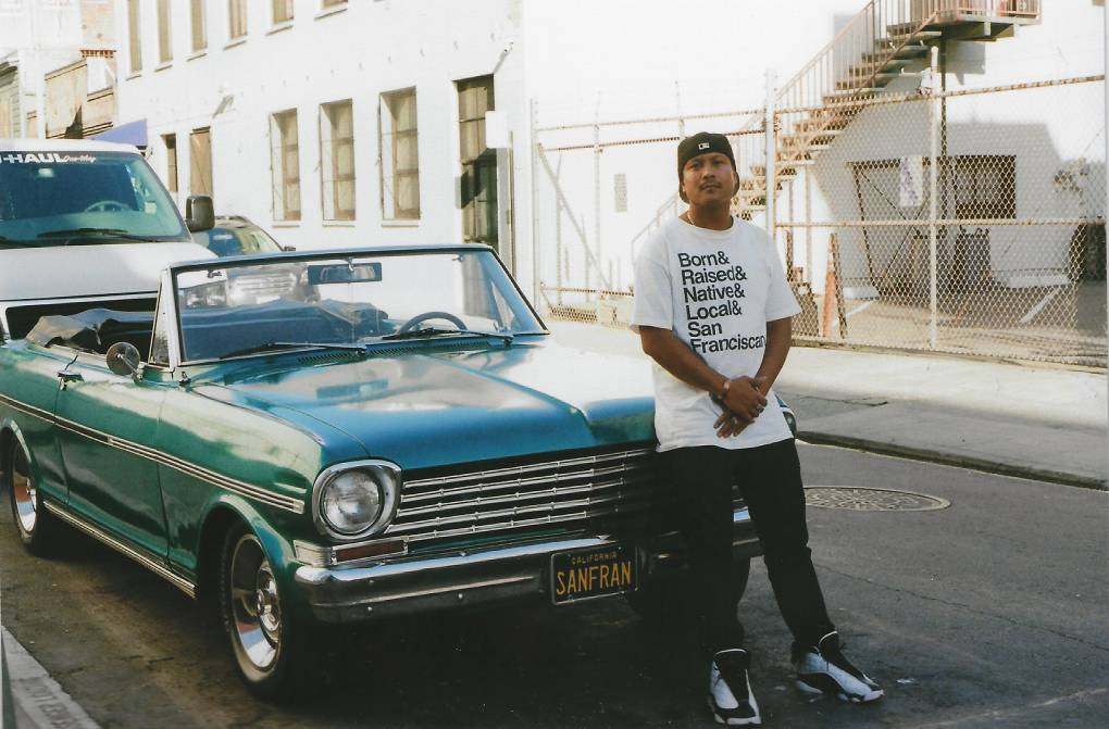 """Harvey Lozada stands in front of a classic American made car with a personalized plate that reads """"San Fran,"""" while wearing a shirt that reads """"Born & Raised & Native & Local & San Franciscan."""""""
