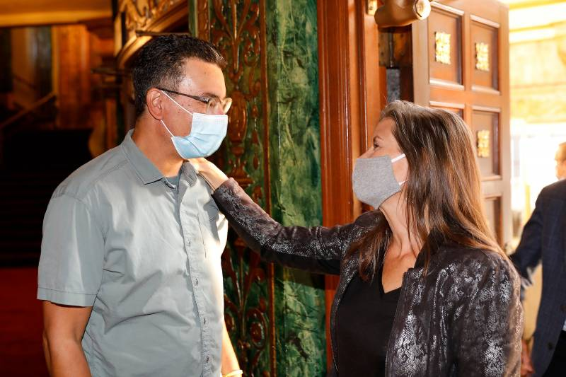 Filmmaker Pete Nicks and Oakland Mayor Libby Schaaf, both wear masks as they share a moment in the lobby of Oakland's Grand Lake Theatre.