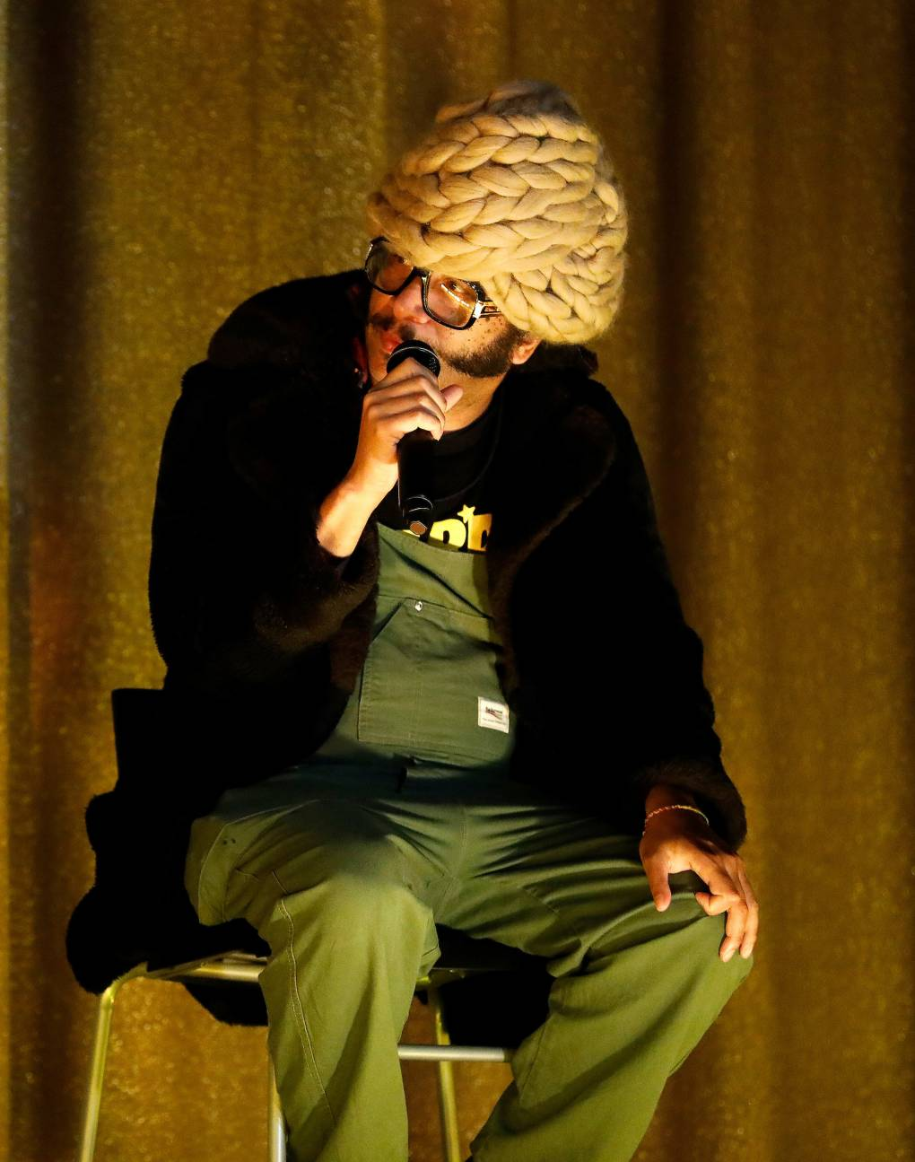Boots Riley, wearing a crochet head piece and glasses, leans forward in his chair to discuss the film Homeroom during a panel discussion at Grand Lake Theatre in Oakland.