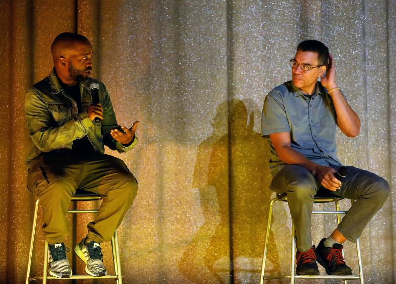 Pendarvis Harshaw and Pete Nicks sit in chairs on stage at Oakland's Grand Lake Theatre discussing the film Homeroom.