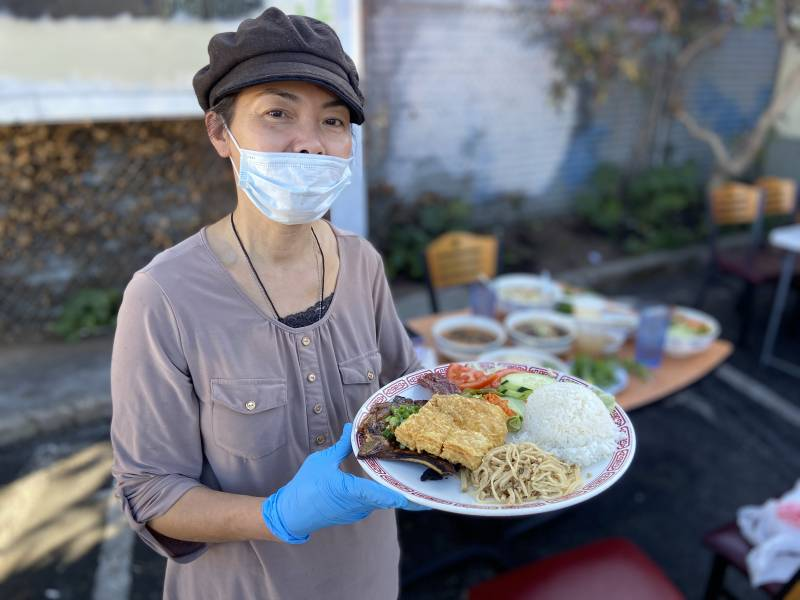The owner of Mekong Restaurant holding a plate of Vietnamese food.