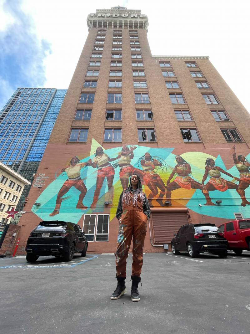 Rachel Wolfe-Goldsmith stands in front of the Tribune Tower in Oakland, which features her large colorful mural of an African American woman dancing
