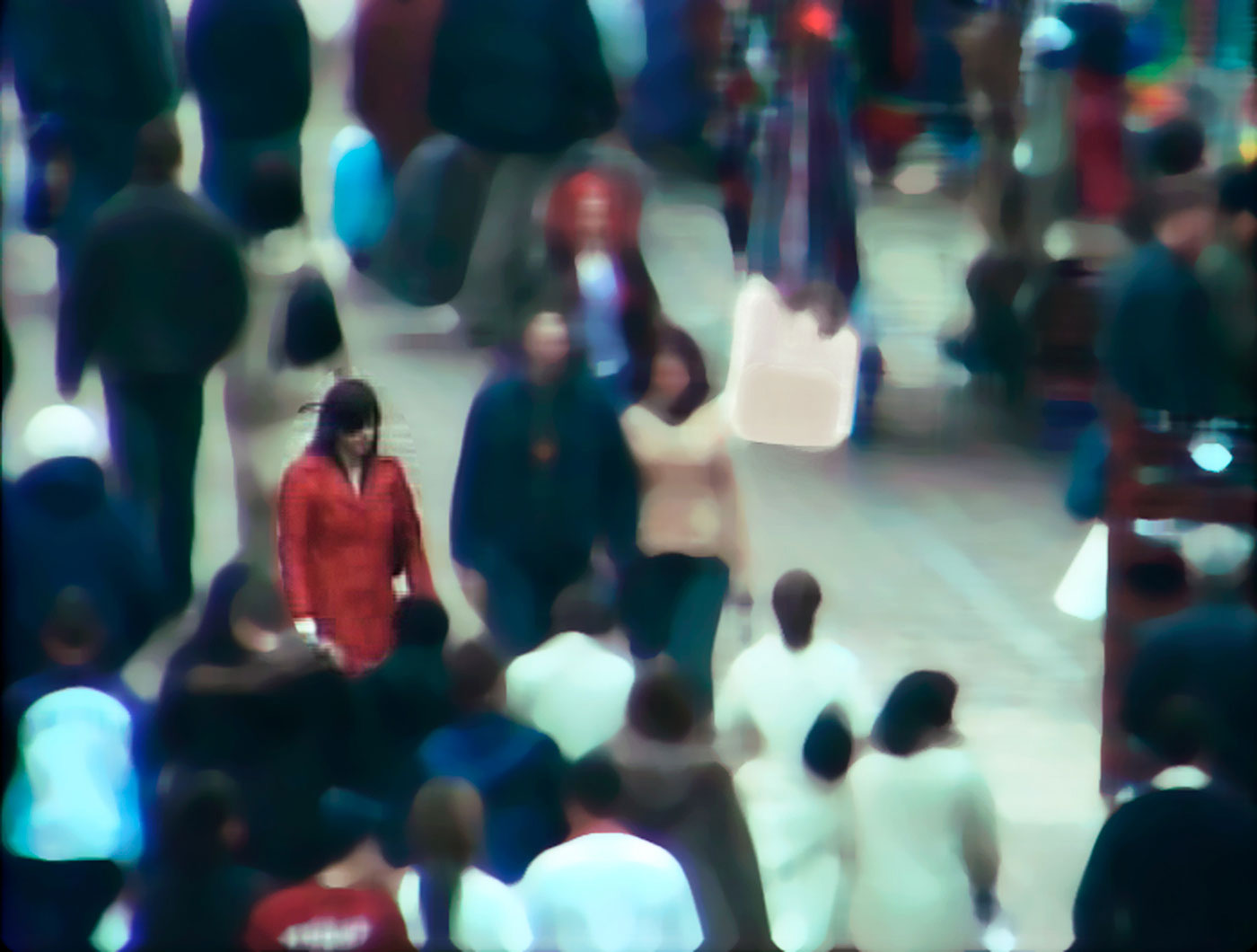 A dark-haired woman in a red coat stands in a crowded street. Only her image is crisp, the other figures have been blurred.