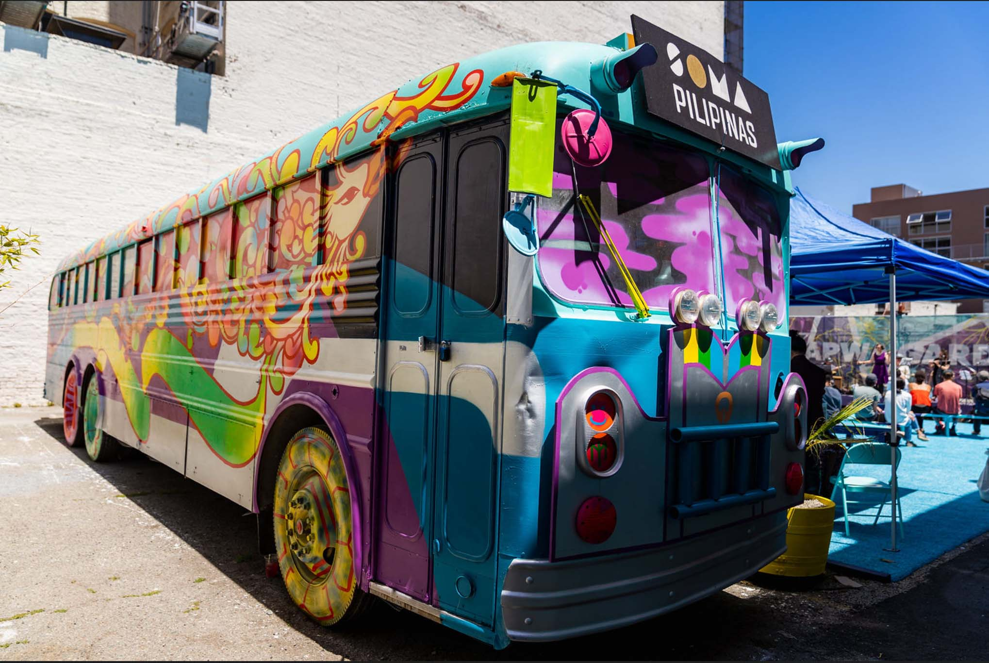 """Colorfully painted bus with a """"SOMA Pilipinas"""" sign in front."""