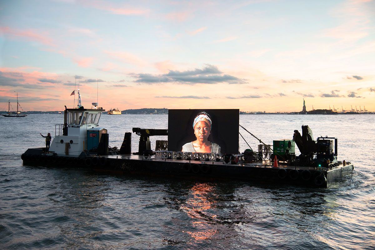 A screen mounted to a floating barge shows a portrait of a woman.