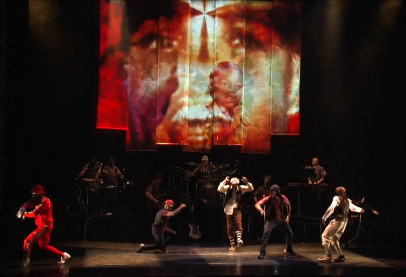 A still from a hip-hop theater production featuring several dancers on a stage of a theater with a big projection screen showing childhood photos of Rennie Harris.