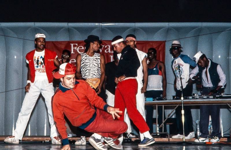 A hip-hop dance and dj crew in the 1980s featuring young male dancers performing on stage while the djs in the back get ready to play a record.