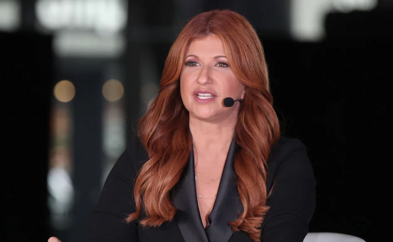 Rachel Nichols, seated at a table, wearing a sleek black suit, acting as a host on ESPN.