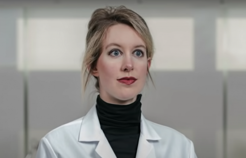 Elizabeth Holmes stares off into the distance with wide blue eyes, hair pulled back in a messy bun, and wearing a lab coat with a black turtleneck underneath.
