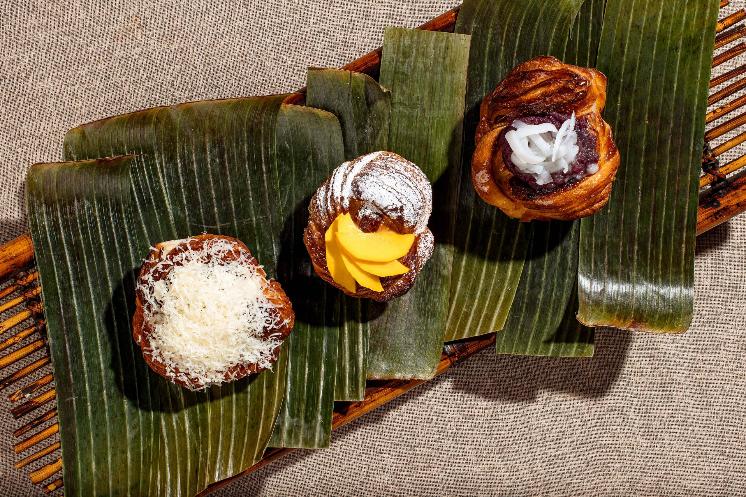 A trio of Filipino pastries, plated on top of banana leaves