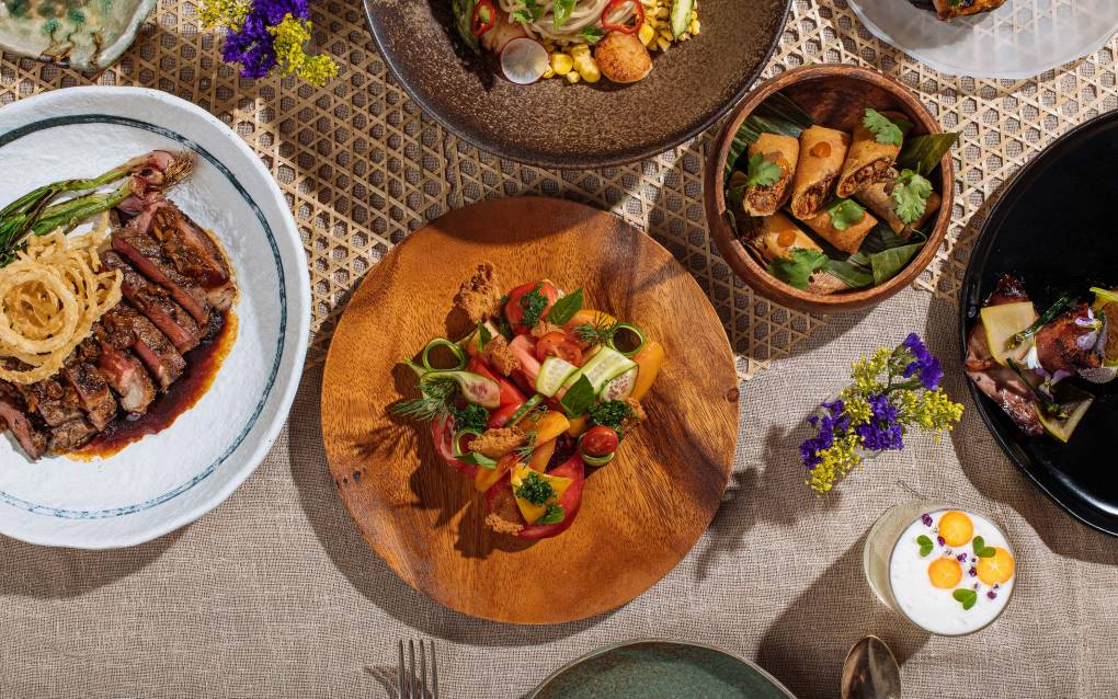 A spread of Filipino dishes, with a tomato and peach salad in the center.