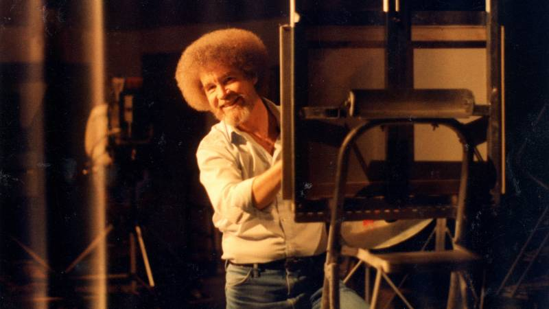 Bob Ross peaks out and smiles from behind a canvas he is painting.