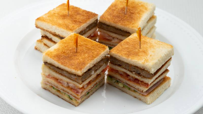 Four mini quadruple-decker sandwiches, each held together with a toothpick on top.