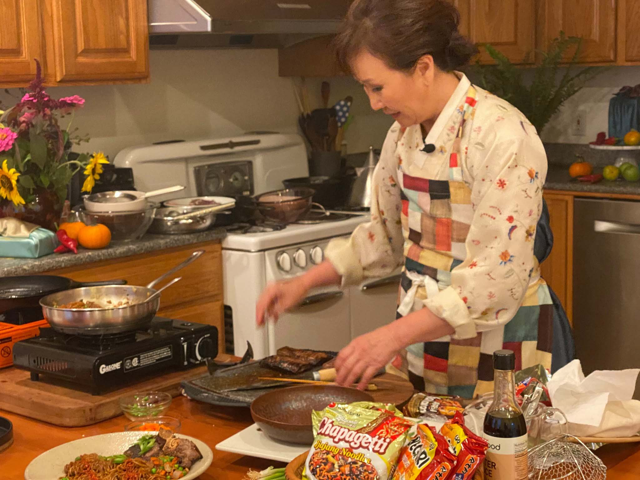 Woman dressed in traditional Korean clothing prepares a dish made with instant noodles.