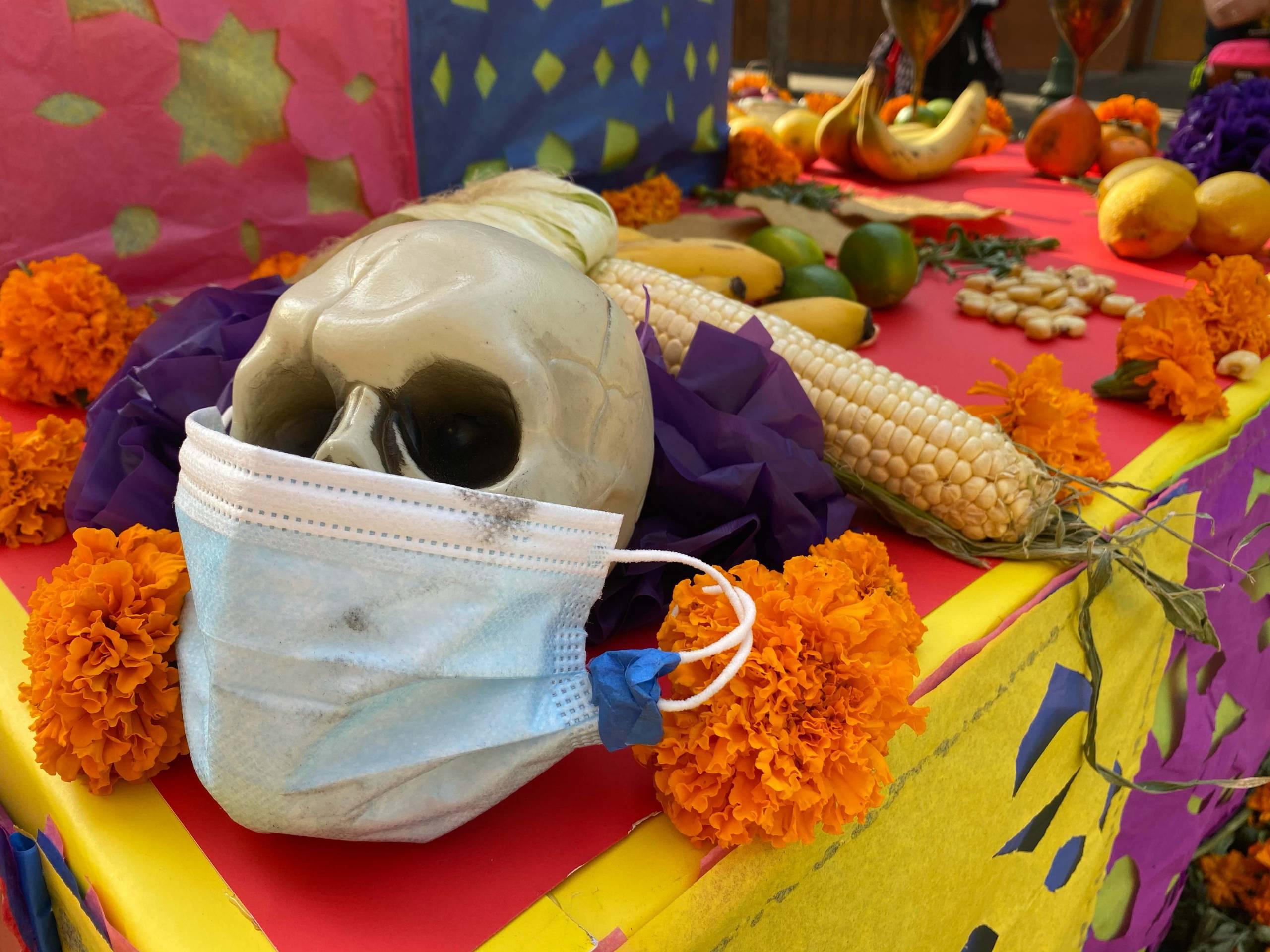 A Día de los Muertos family altar display featuring a skull wearing a face mask.