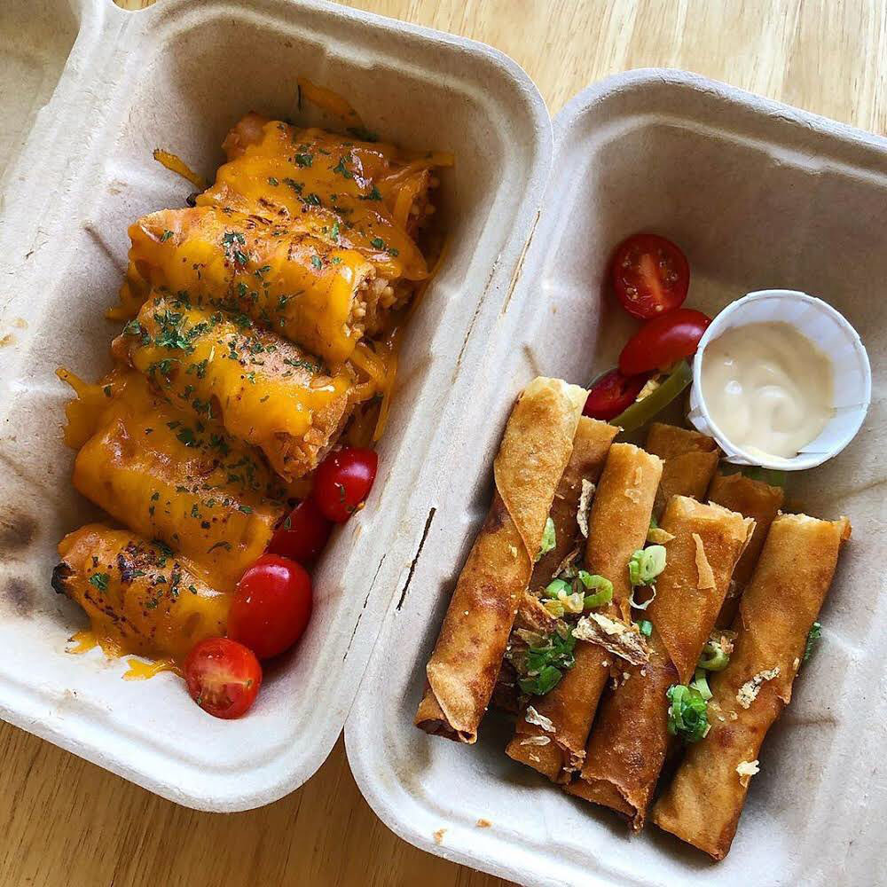 Two different kinds of lumpia in a cardboard takeout container.