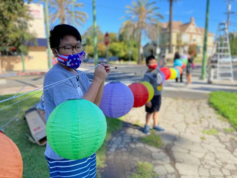 Schoolchildren in face masks stringing up paper lanterns in Clinton Park, Oakland.