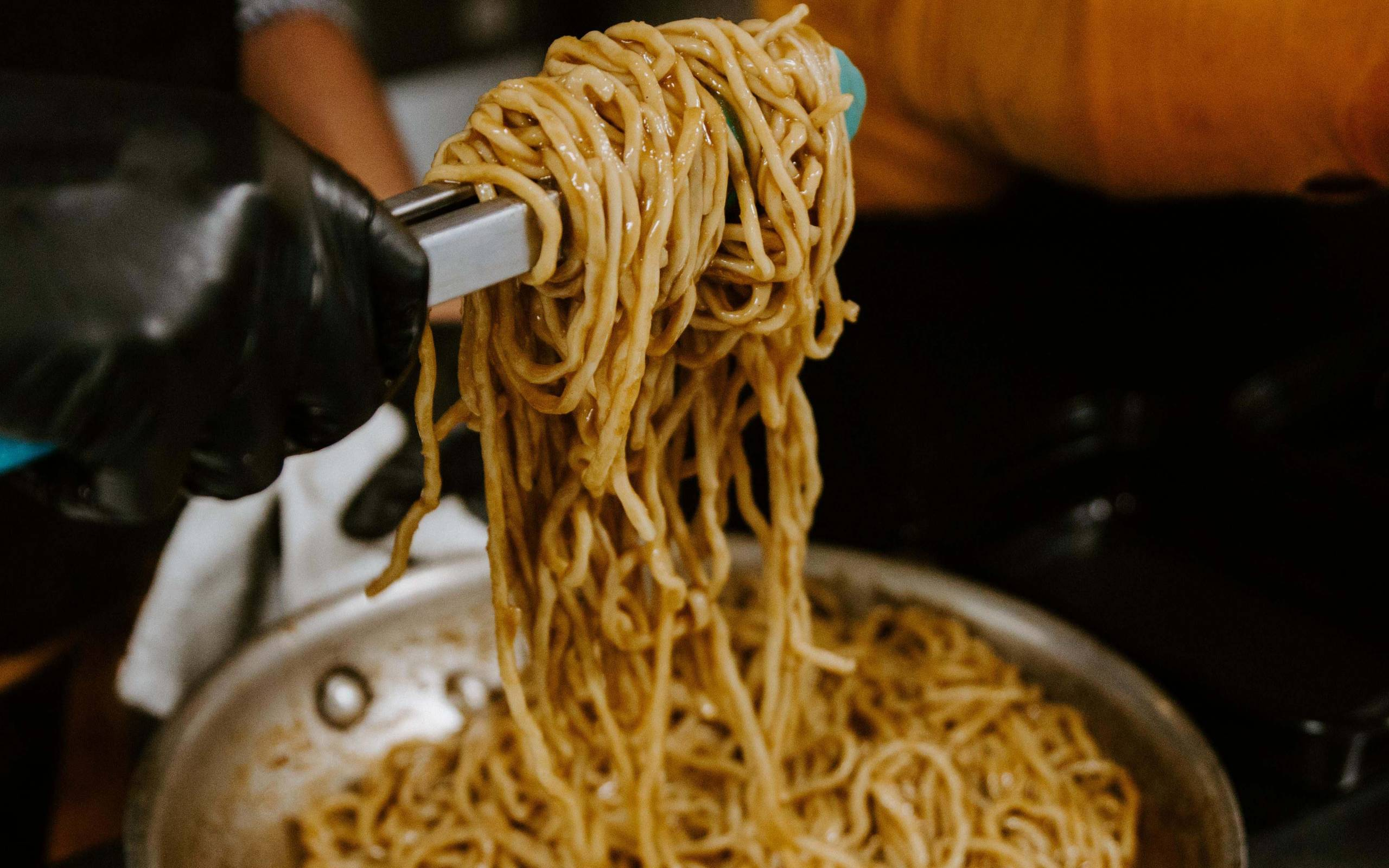 Saucy garlic noodles are mixed with a pair of tongs at Noodle Belly.