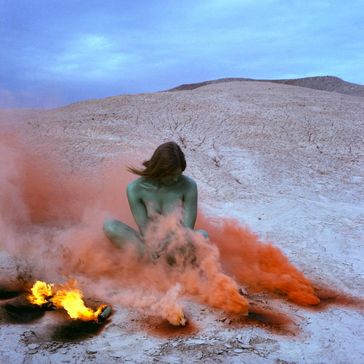 Woman with green skin sits in a cloud of orange smoke.