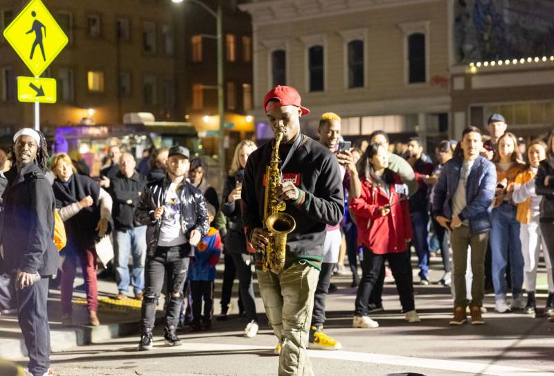 A saxophonist plays on the street at a street fair in Oakland.