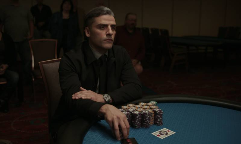 A sharply dressed man sits at a green felt table, many stacks of gambling chips lined up before him.