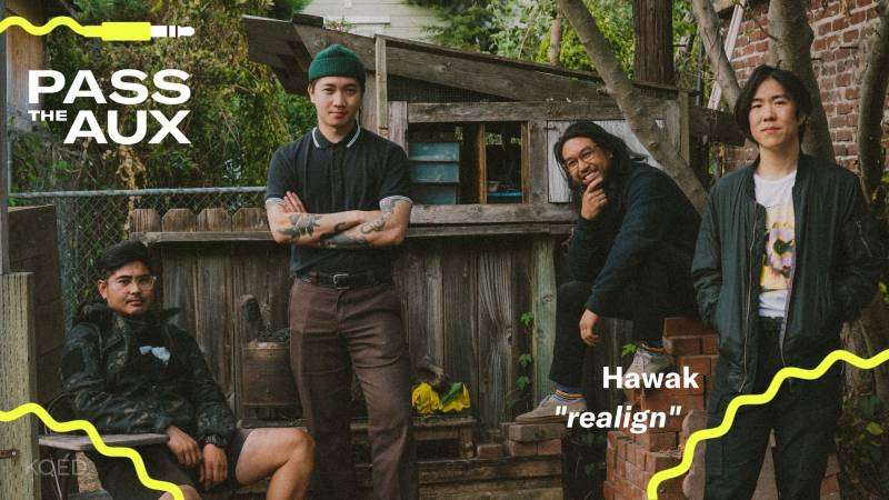 Four men pose in a cluttered yard.