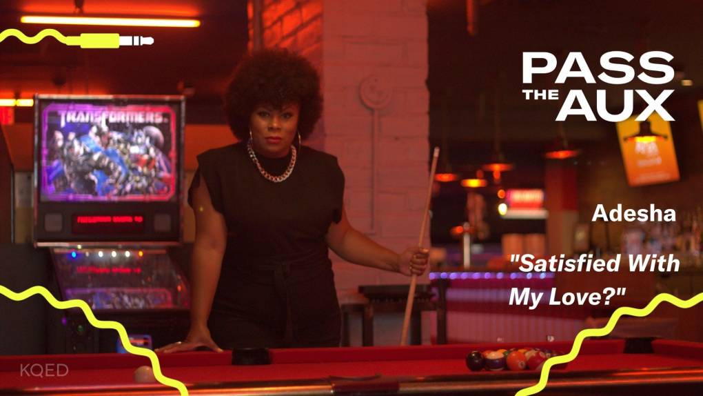 A singer stands in a dark pool hall with an old arcade machine.