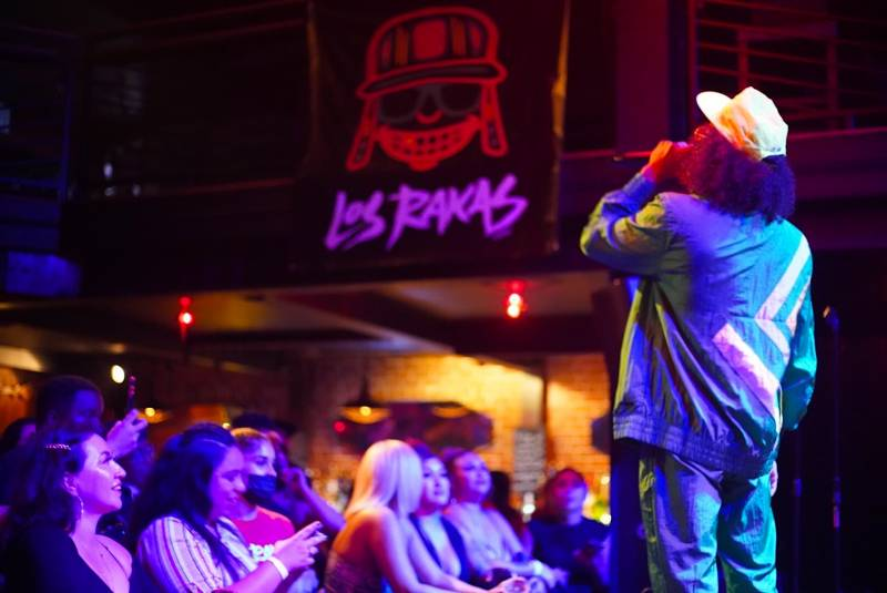 Raka Rich wears a turquoise jogging suit and a hat as he performs in front of a crowd at New Parish in Oakland.