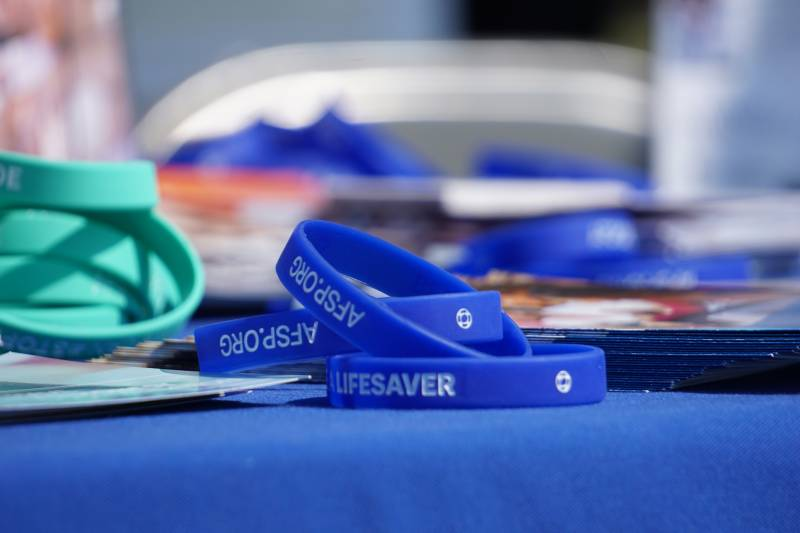 """The word """"Lifesaver"""" is inscribed on a wristband that sits on a table at a prior Out Of The Darkness event."""