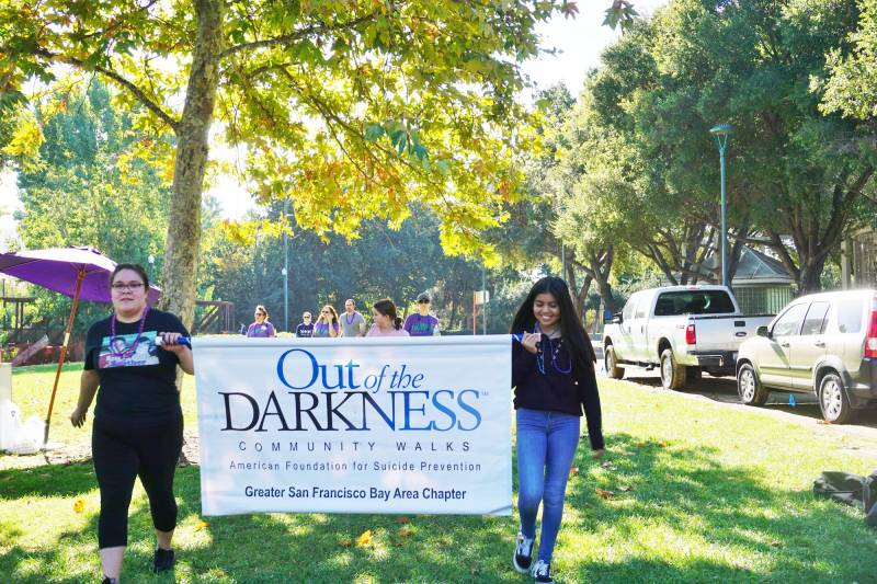 Two volunteers walk through a grassy area while holding a banner that reads 'Out Of The Darkness'.