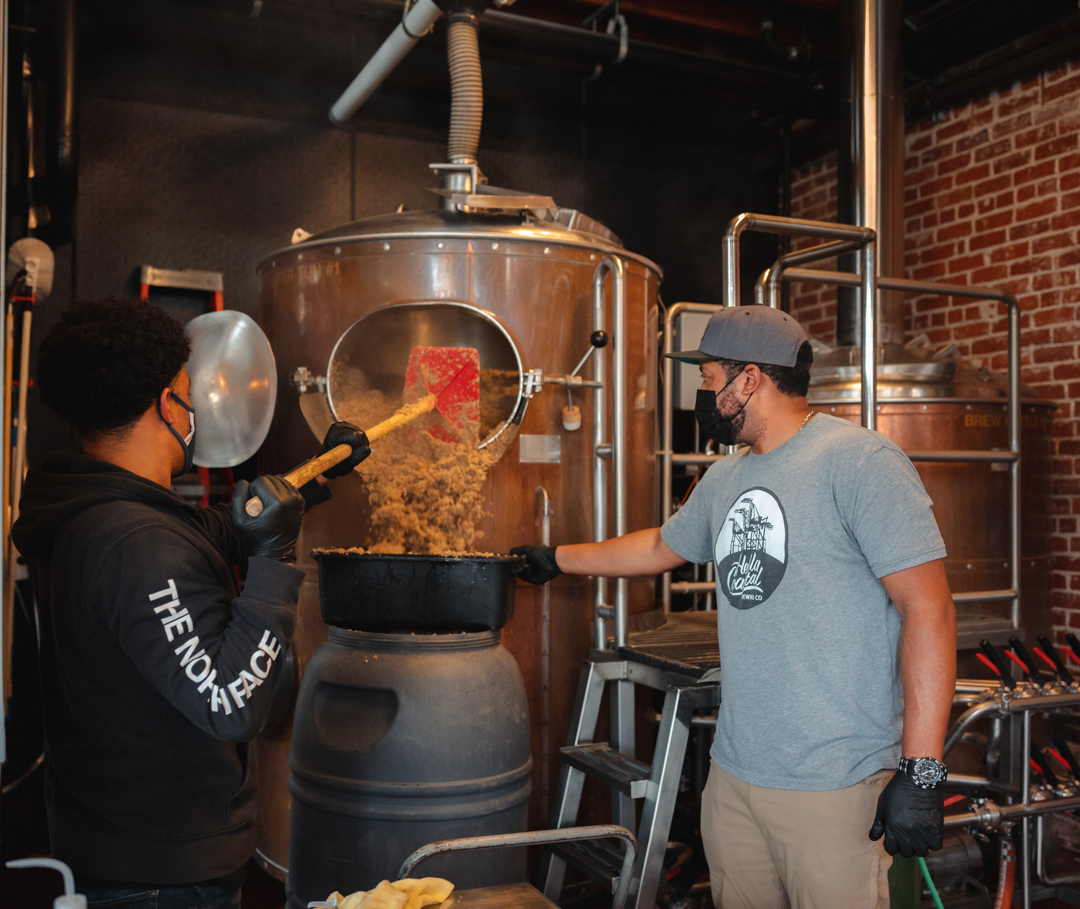 Two men making beer with professional brewing equipment; one wears a visor for protection.