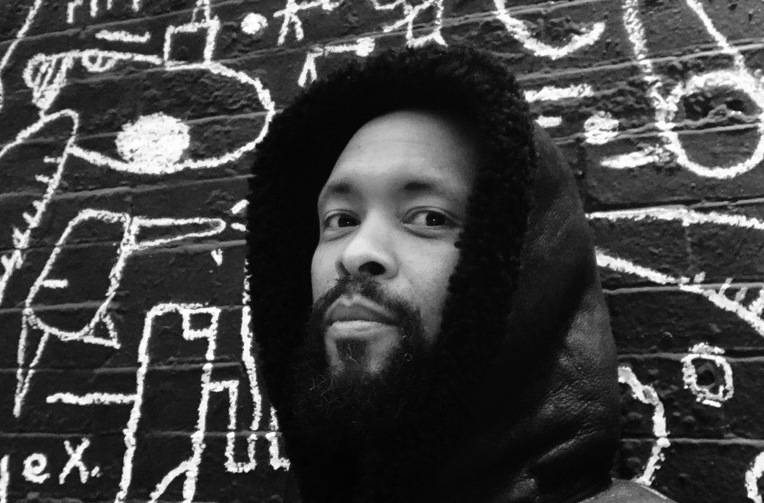 In a black and white photo, Tajai Massey posses in a black hoodie in front of an artistic background that shows what appear to be painted squiggles and designs