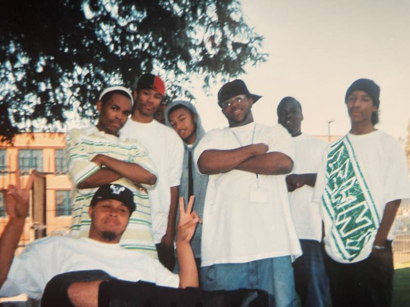 Raka Rich (center in the grey hoodie) stands with a number of young artists outside of East Oakland's Youth Uprising (circa 2005).