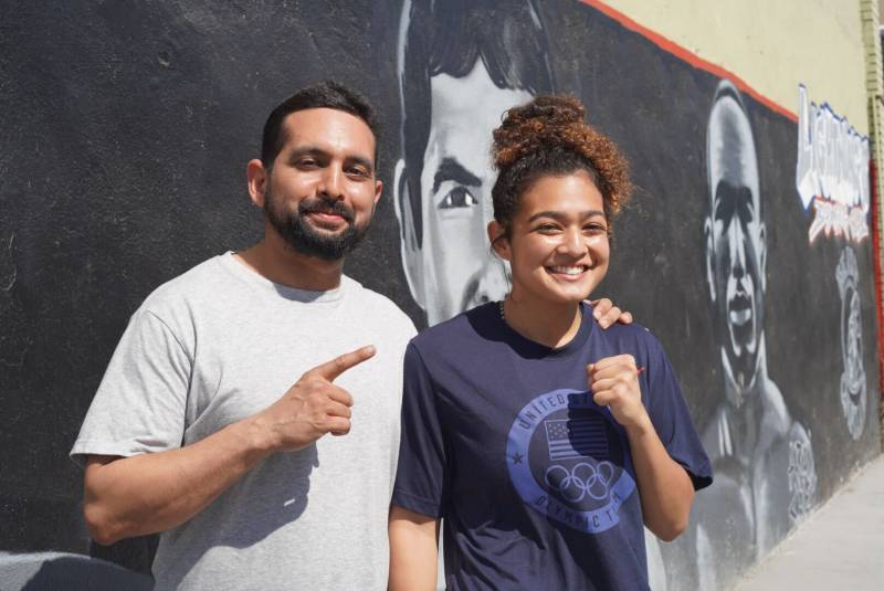Outside of Lightning's Boxing Club in East Oakland Mario Bamberger and Daisy Bamberger pose for a photo in front of a mural of boxing legends.