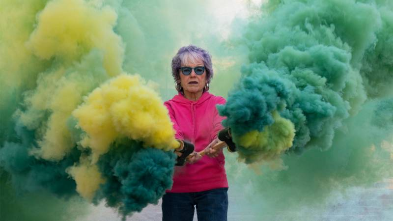 Older woman holds sticks with green and yellow smoke coming out.