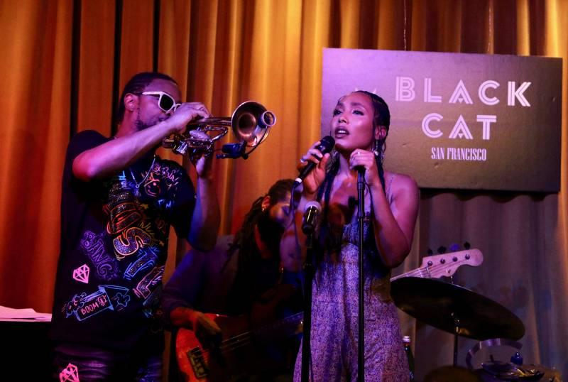 A man in sunglasses plays the trumpet while a woman sings into a microphone.