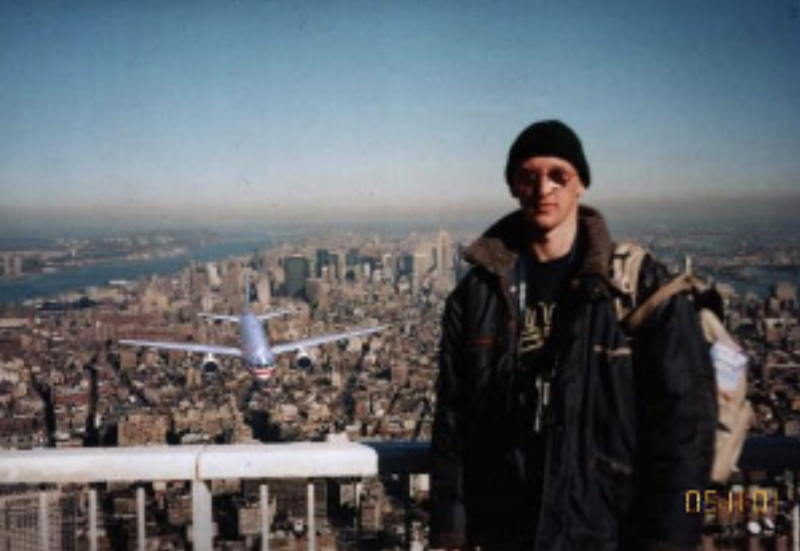 A man stands on the World Trade Center's observation deck with New York City's skyline behind him. In the left of the photo is an approaching commercial airplane.