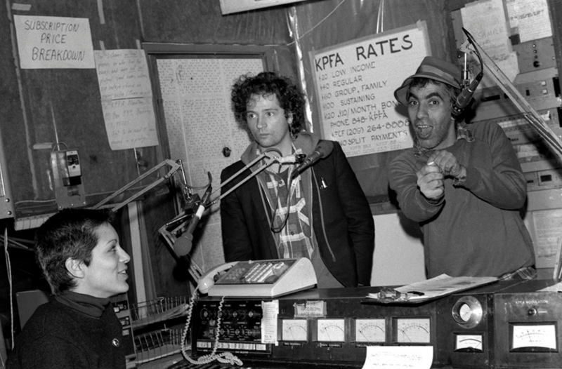 A woman with very short, cropped hair sits behind a radio mic and audio equipment, including an old fashioned switchboard telephone. Two men stand in front of her, also with radio microphones.
