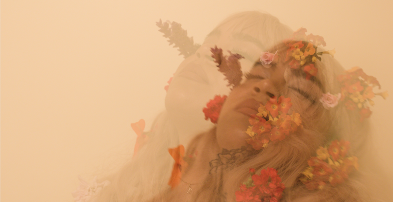 A floral arrangement adorns musician Xiomara as she closes her eyes and poses in a double-layered portrait image.