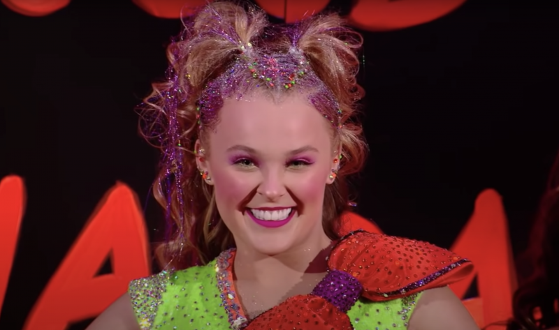 JoJo Siwa, wearing a neon green top with giant orange bow on the shower, smiles with her hair full of pink glitter.