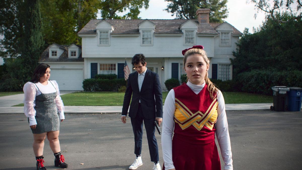 Three teenagers on a suburban street, one in a cheerleading uniform.